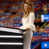 Melania Trump in a white, fitted dress with dramatic sleeves by London-based designer Roksanda Ilincic.
