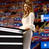 Melania Trump, wearing in a white, fitted dress with dramatic sleeves by London-based designer Roksanda Ilincic.