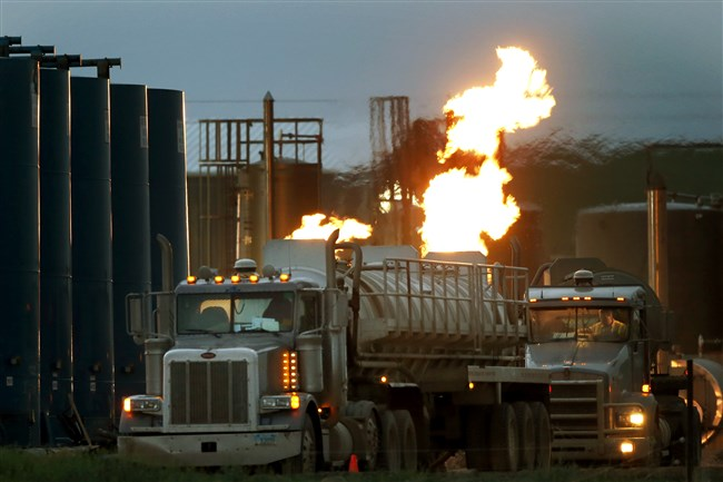 Drivers and their tanker trucks, capable of hauling water and hydraulic fracturing liquid, line up near a natural gas burn off flame and storage tanks in Williston, N.D.
