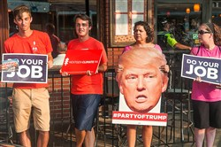 Wilson Juring and Bobby Maggio, representatives of Nextgen Climate PA ,join Planned Parenthood volunteers Jessica Durkin and Robin Felder to protest the reelection of Pa. Sen. Pat Toomey on Tuesday outside of his campaign stop in the Strip District.