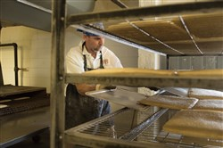 A worker at Tomanetti Food Products bakery in Oakmont moves pizza crusts from the oven on Wednesday.