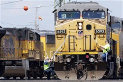 A train operator, left, dismounts a Union Pacific locomotive, while another operator climbs up, at a rail yard in Council Bluffs, Iowa. Union Pacific reported financial results Thursday, July 21.