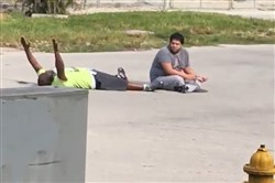 This is a still image taken from the cell phone recording that purports to show Charles Kinsey while trying to calm down an autistic patient who had run away from his North Miami assisted living facility when police arrived. A bystander filmed their interactions on July 18, before Mr. Kinsey, left, who was lying on the ground with his hands up, was shot.
