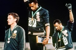 U.S. athletes Tommie Smith, center, and John Carlos, right, raise their fists in protest while on the medal stand for the 200 meter run at the 1968 Olympics in Mexico City.