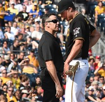 Pirates athletic trainer Ben Potenziano talks with Tyler Glasnow before the pitcher left in the fourth inning Saturday against the Phillies.