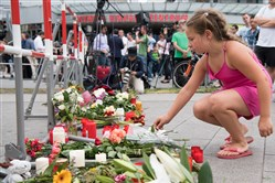 A girl adds flowers to a public memorial in front of the Olympia shopping center Saturday were a mass shooting left  nine people dead the day before in Munich, Germany.