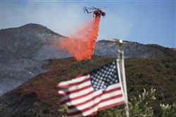 Framed by a burned-over hillside, rear, and an American flag in the foreground, a helicopter drops fire retardant ahead of advancing flames as a wildfire approaches Placerita Canyon in Santa Clarita, Calif., on Monday.