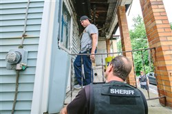 Members of the fugitive squad at the Allegheny County Sheriff's Office attempt to get inside a house in Knoxville to arrest a man wanted on a family court warrant.
