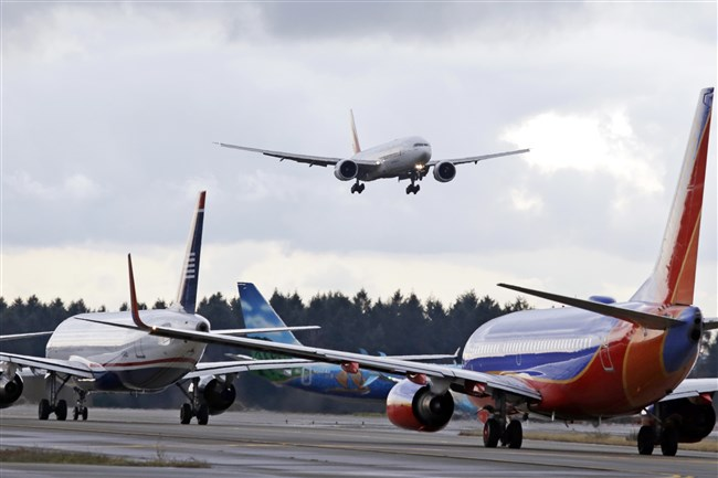 In this Dec. 16, 2015, file photo, a passenger jet comes in for a landing and in view of a line of planes waiting to takeoff, at Seattle-Tacoma International Airport.
