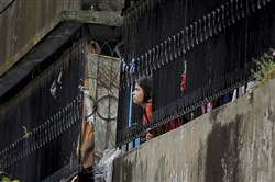 A Bangladeshi girl watches from a nearby building after a five-story building was raided by police in Dhaka on Tuesday.