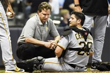 Pirates catcher Francisco Cervelli, right, is looked at by assistant athletic trainer Ben Potenziano, left, after being injured during the eighth inning Friday against the Brewers.