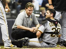 Pirates catcher Francisco Cervelli is looked at by athletic trainer Todd Tomczyk after being injured during the eighth inning Friday at Miller Park.