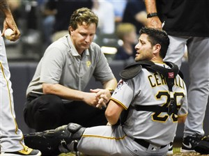Pirates catcher Francisco Cervelli is looked at by assistant athletic trainer Todd Tomczyk after being injured in the eighth inning against the Milwaukee Brewers July 29, 2016.