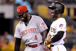 Andrew McCutchen, right, jokes with the Reds' Brandon Phillips after stealing second base in the sixth inning Friday at PNC Park.