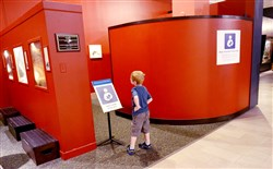 A curious child checks out the baby friendly privacy area located near the Discovery Basecamp in the Carnegie Museum of Natural History.