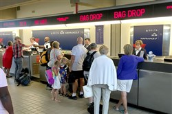 Travelers wait to check in at the Delta ticket counter at Pittsburgh International Airport in this photo from August 2016. Airlines operating out of Pittsburgh International Airport will see a big reduction in fees next year under a $108.9 million budget adopted Friday.