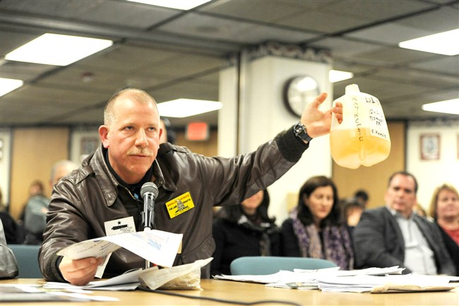 Craig Stevens of Silver Lake Township, Pa., holding a jug of contaminated water from a neighbor's home in Dimock, testifies during a Pennsylvania House of Representatives hearing held in Washington, Pa. in February 2013