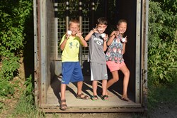 From left, Bryce Kameg, 9, Carson Ruffing, 9, and Kamryn Kameg, 12, pose for a photo in one of the animal traps while enjoying some ice cream.