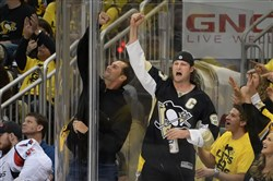 The Pirates' Gerrit Cole (in Pens jersey) cheers on the Penguins at the Consol Energy Center in Pittsburgh.