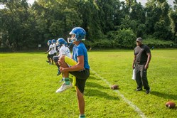 Westinghouse High School football coach Monte Robinson works with his players at a preseason practice last week.
