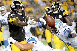 Steelers receiver Sammie Coates loses the football and faces an impending blow from a Detroit defender.