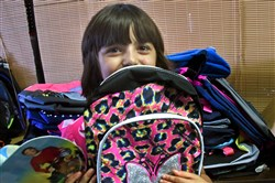 "Melissa Karimora of Bethel Park, proudly holds up her new backpack that she picked out in last year's  ""Back-to-School Drive""  cooridnated by the South Hills Interfaith Movement."