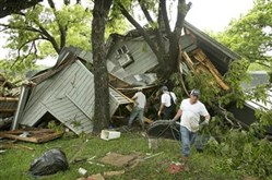 Donora residents clear debris after a tornado Sunday knocked down a house.