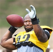 The Steelers' James Harrison drops back to pass during afternoon workouts Aug. 7 at Saint Vincent College.