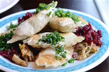 Sauerkraut and mushroom pierogis and the smoked potato roast parsnip and mustard greens pierogis served with beets, sauce and chive at Apteka.