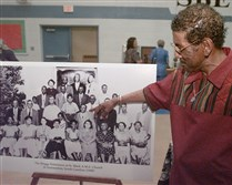 Harry Briggs Jr., of New York, points to his father in a 1949 group photo in 2002.