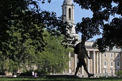 A Penn State University student walks in front of Old Main on main campus in State College.