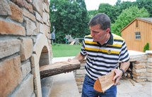 Aldo Betta stacks pieces of wood in an oven that he constructed in his back yard. He used components from HarbinsonWalker International, a company that manufactures bricks and mortar for industrial furnaces used in steel, glass and aluminum production.