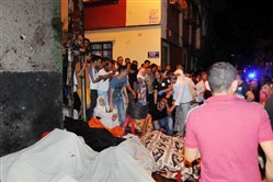 People react after an explosion in Gaziantep, southeastern Turkey, early Sunday. Gaziantep Province Gov. Ali Yerlikaya said the deadly blast, during a wedding near the border with Syria, was a terror attack.