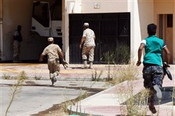 Forces loyal to Libya's U.N.-backed Government of National Accord run toward a building in Sirte, east of the capital Tripoli, as they comb through residential neighborhoods that were previously controlled by the Islamic State group, clearing the area of booby traps and car bombs Monday.