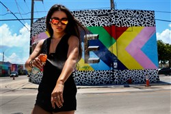 Carrie Abraham uses mosquito spray before walking through the Wynwood neighborhood in Miami, ground zero of the Zika outbreak in the U.S., on Tuesday.