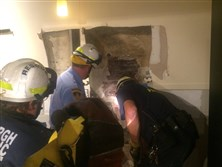 Rescuers work to free a Pitt student who got himself wedged between two buildings.