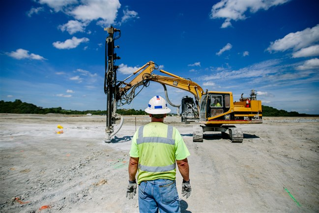 Kevin Helsley, a blaster for Wampum Hardware, watches as blasting holes are drilled on the site of a natural gas power plant in Smithton on Aug. 24. About half a dozen years after Tenaska first proposed building natural gas fired generating plant in Westmoreland County, the project is starting construction. The power plant will generate about 300 construction jobs over a three year period and, when operational, will make enough electricity to power almost a million homes.