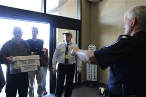 A Jefferson Parish sheriff's deputy, right, tells protesters John Clark, carrying a box with a copy of a petition against federal oil lease sales, and Blake Kopcho, second from left, that they cannot enter the building where the leasing agency has offices, Aug. 23, in Harahan, La. The protest was Tuesday, a day before the Bureau of Ocean Energy Management has scheduled a lease sale for Gulf of Mexico water bottom off of Texas. Legal observer Bill Qugley, wearing hat, said Clark and Kopcho were among four demonstrators later arrested on a charge of trespassing.