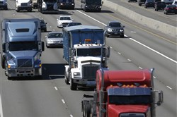 Trucks and automobiles head north on Interstate 5 through Fife, Wash. The federal government wants to use a device to limit how fast trucks, buses and other large vehicles can drive on the nation's highways.