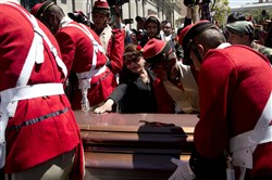 A woman reaches out Friday to touch the coffin containing the remains of Rodolfo Illanes, Bolivia's deputy minister of internal affairs, outside the government palace in La Paz.