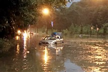 A car sits partially submerged Sunday on Washington Boulevard in Pittsburgh's East End neighborhood. The flood response team pulled people out of two vehicles with throw ropes. Officer Andre Wright, with the city's Zone 5, swam out to assist. Everyone escaped unharmed.