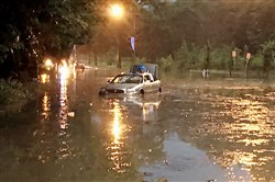 A car sits partially submerged Sunday on Washington Boulevard in Pittsburgh's East End neighborhood. The flood response team pulled people out of two vehicles with throw ropes.