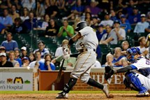 Josh Harrison hits a sacrifice fly in the 13th inning Monday at Wrigley Field.