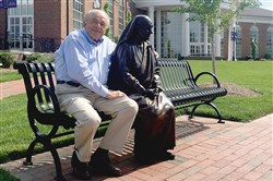 Wash Gjebre with a statue of Mother Teresa on campus of High Point University in North Carolina. Below, Mother Teresa in 1993, at age 85.