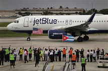 Workers and officials watch Wednesday as JetBlue Flight 387 prepares for take off as it becomes the first scheduled commercial flight to Cuba since 1961 in Fort Lauderdale, Fla.