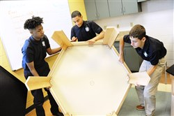 Ninth-graders, from left, Leelee Thompson, Phillip Solomon and Dylan Stone of Holy Family Academy in Emsworth, assemble a chemistry lab table on the first day of school on Thursday. Students assemble their own wooden desks and chemistry lab tables at the start of the new year.