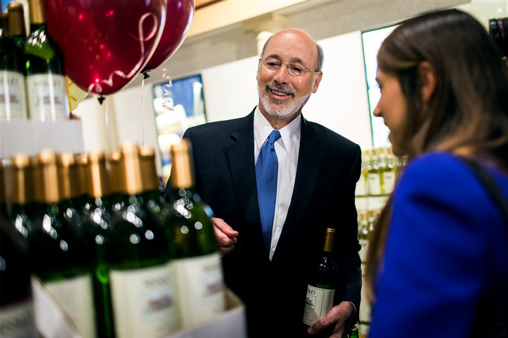 Pennsylvania Governor-2 Gov. Tom Wolf purchases wine and beer after a press conference in September to introduce the sale of wine at Wegmans in Mechanicsburg, Pa.