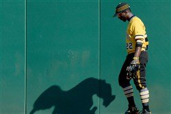 The Pirates' Andrew McCutchen walks along the warning track after watching a home run by Brewers' Chris Carter go over the wall in the ninth inning Sunday at PNC Park.