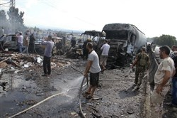 Syrian security forces, emergency services and residents look at the remains of burned vehicles at the site of a bombing in Tartus on Sept. 5.