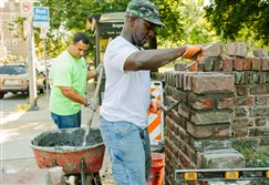 Mortar men: Abdulah Bey, right, and Dylan Seddon, both with Pittsburgh Public Works, at work on a border wall for Allegheny Commons' West Park.